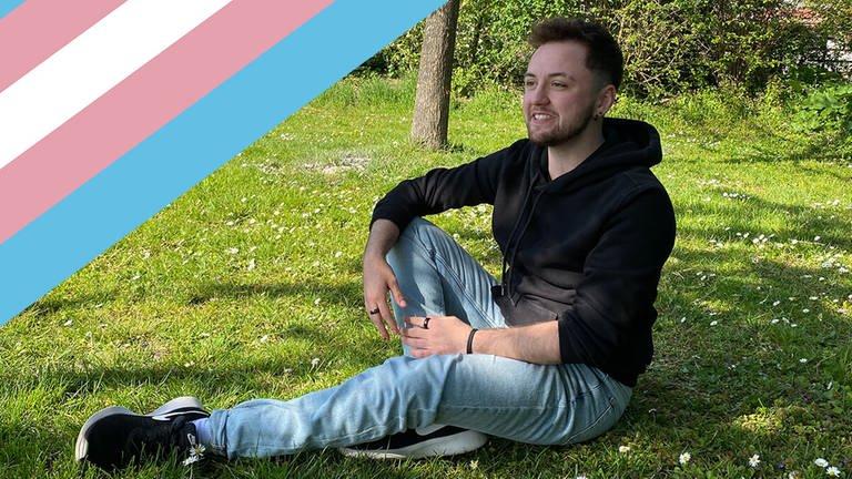 Trans*Mann Maximilian Löffler sitzt in einer Wiese im Freien. In der Ecke ist eine Trans* Flagge zu sehen.