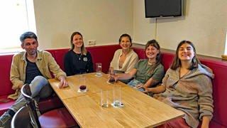 Fünf Mitglieder des feministischen Dorfgeflüster-Kollektivs sitzen bei einem ihrer Treffen um einen Tisch.  (Foto: SWR, DASDING, Hardy Faißt)