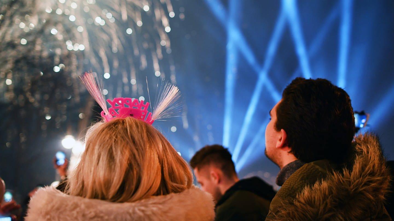 Ein Paar betrachtet an Silvester ein Feuerwerk. (Foto: picture-alliance / dpa, picture alliance / Jens Kalaene)
