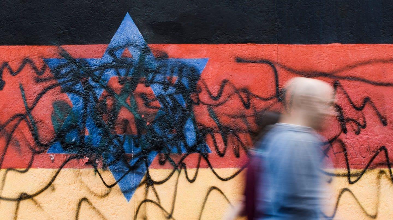 Beschmiertes Wandbild, das die schwarz-rot-goldene Deutschlandfahne mit einem blauem Davidstern zeigt
