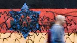 Beschmiertes Wandbild, das die schwarz-rot-goldene Deutschlandfahne mit einem blauem Davidstern zeigt (Foto: dpa Bildfunk, picture alliance/dpa   Carsten Koall)