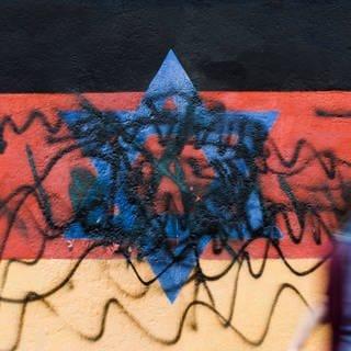 Beschmiertes Wandbild, das die schwarz-rot-goldene Deutschlandfahne mit einem blauem Davidstern zeigt (Foto: dpa Bildfunk, picture alliance/dpa | Carsten Koall)