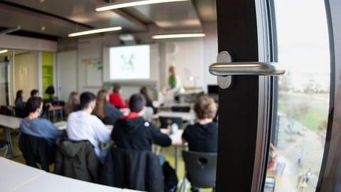 Schülerinnen und Schüler nehmen mit Mund- und Nasenschutz am Unterricht teil (Foto: dpa Bildfunk, picture alliance/dpa | Matthias Balk)