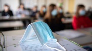 Eine Maske liegt im Unterricht auf Unterlagen, während im Hintergrund Schülerinnen und Schüler sitzen (Foto: dpa Bildfunk, Picture Alliance)