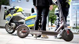 Ein E-Scooter steht vor einem Polizeimotorrad. (Foto: dpa Bildfunk, picture alliance/dpa | Martin Gerten)
