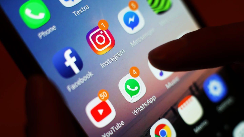 Ein Blick auf ein Smartphone mit den verschiedenen Social Media Apps, wie Facebook, Instagram, YouTube und WhatsApp.