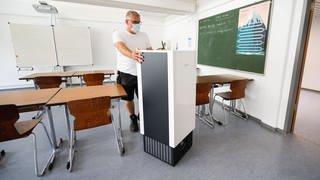 Ein Hausmeister schiebt einen recht großen Luftfilter durch ein Klassenzimmer. (Foto: dpa Bildfunk, picture alliance/dpa | Julian Stratenschulte)