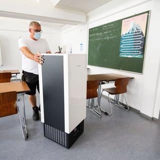 Ein Hausmeister schiebt einen recht großen Luftfilter durch ein Klassenzimmer. (Foto: dpa Bildfunk, picture alliance/dpa   Julian Stratenschulte)