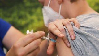 Ein Junge bekommt mit einer Spritze eine Impfung in die Schulter. (Foto: dpa Bildfunk, picture alliance/dpa | David Young)