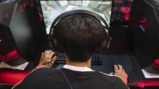 Ein Junge sitzt vor einem Gaming-PC, hat Kopfhörer auf und spielt ein Computerspiel. (Foto: imago images, IMAGO / ZUMA Wire)
