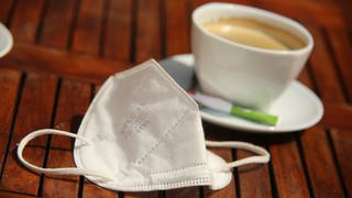 Eine FFP2-Maske liegt neben einer Tasse Kaffee auf einem Tisch. (Foto: dpa Bildfunk, picture alliance/dpa/dpa-Zentralbild | Matthias Bein)